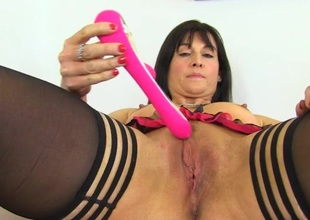 Dressy milf slips a pink toy into her perfect pussy