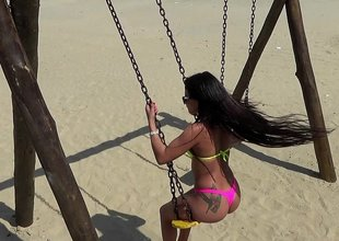 Puckish babe swings outdoor onwards beach