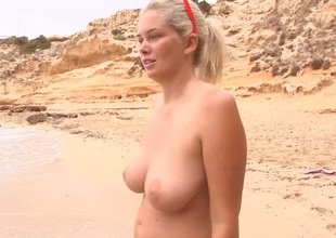Curvy topless golden-haired skipping stones on an obstacle beach