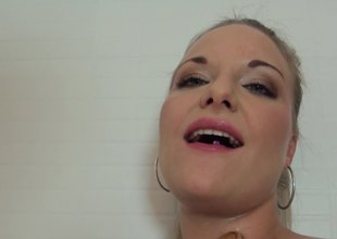 A blonde takes a shower during which she massages her moist cunt