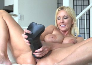 An heavy black dildo destroys her taut shaved pussy
