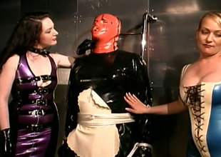 Duo beautiful mistresses dress their serf up apropos latex