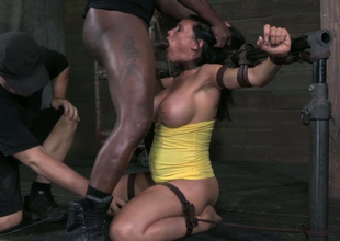 Belted brunette in yellow dress is belted together with stands on knees while boastfully BJ